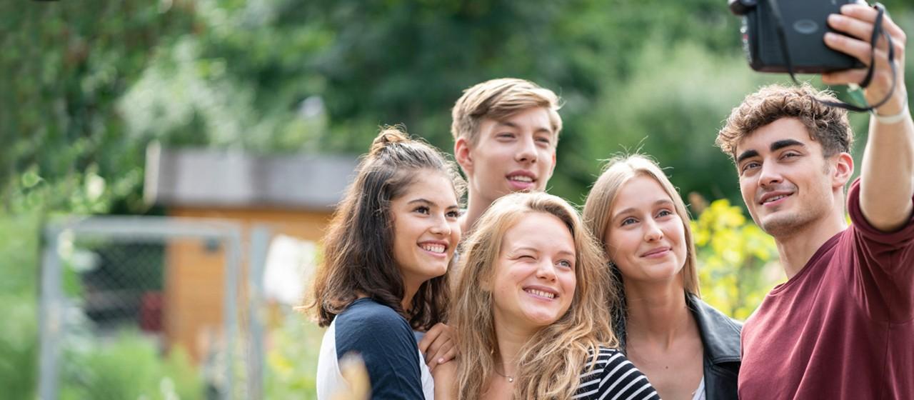 5 junge Menschen stehen lachend an einer Bushaltestelle und halten ihre Smartphones in den Händen