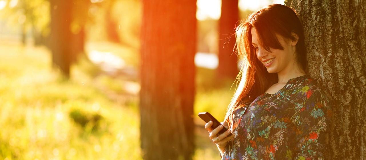 Frau schaut angelehnt an  Baum auf ihr Handy
