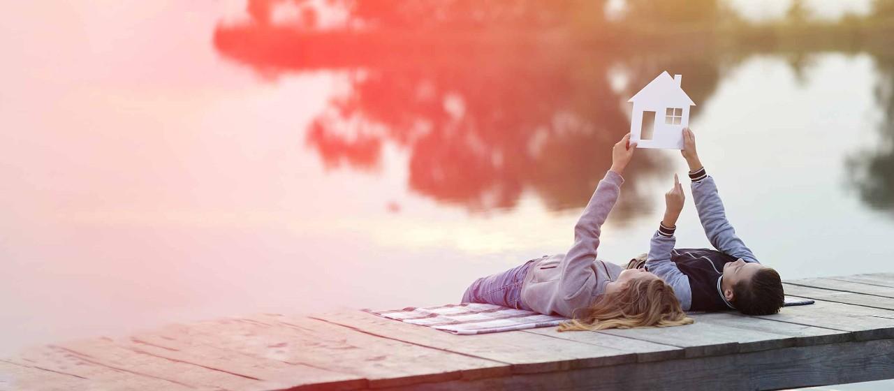 Zwei kleine Kinder, die auf einem Steg am Bodensee liegen und von Ihrem Traumhaus träumen