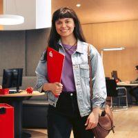 Mann springt mit Fallschirm und Schwimmflügeln vom 1-Meter-Brett im Freibad