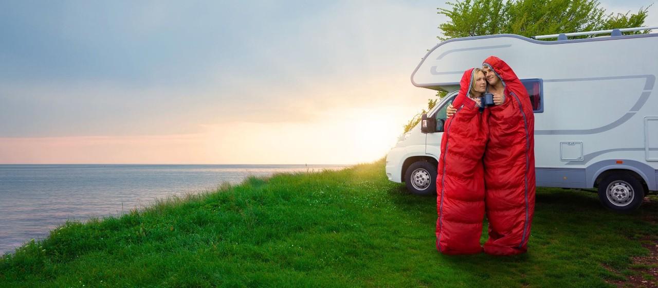 Frau sitzt auf Sofa und bezahlt beim Online-Shopping mit ihrer Mastercard Gold (Kreditkarte)