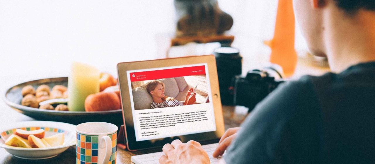 Mann liest Newsletter auf Tablet